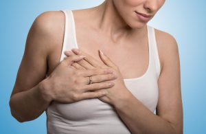 Closeup cropped portrait young woman with breast pain touching chest colored isolated on blue background